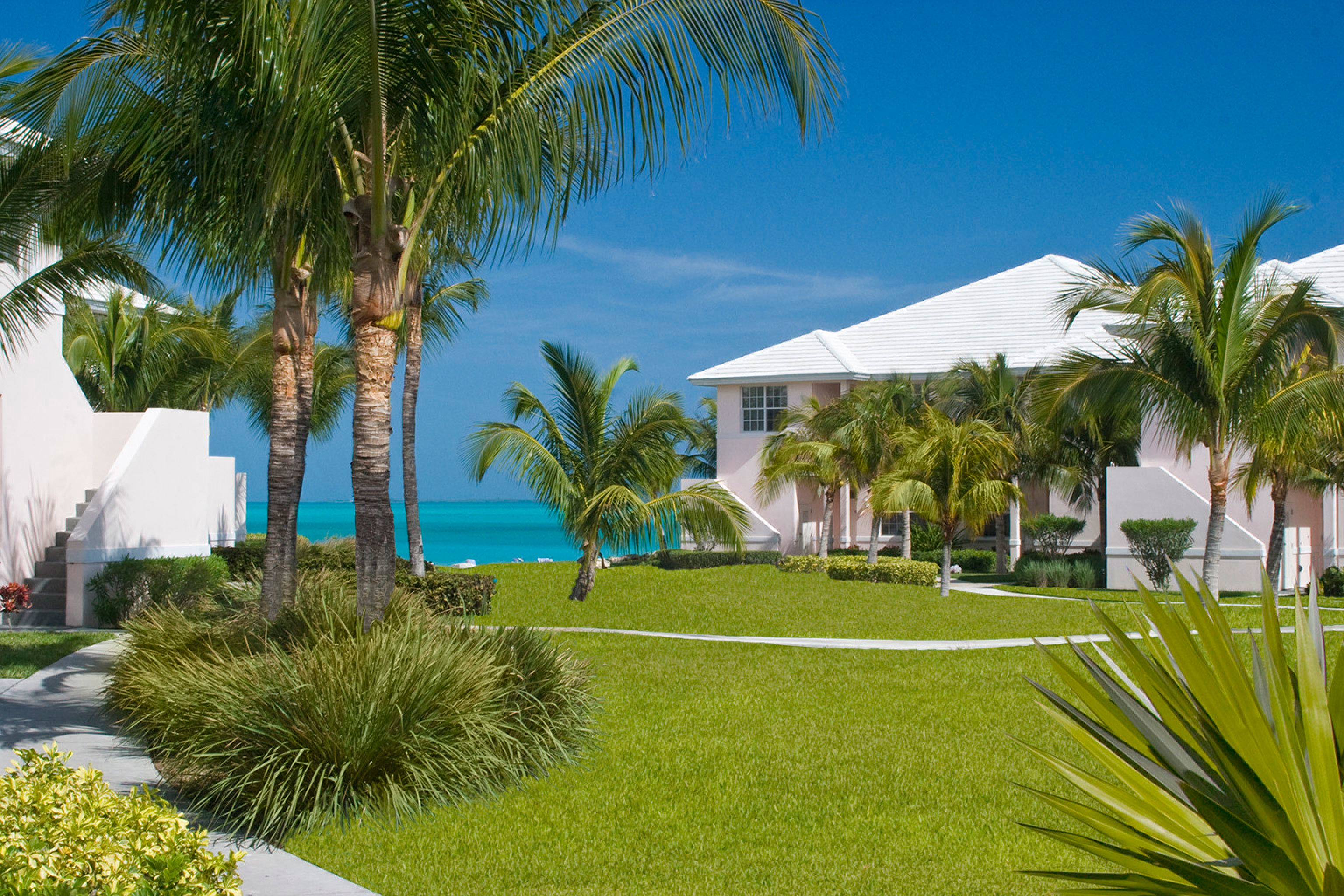 Beachfront Exterior Grounds Resort tree palm grass sky property swimming pool palm family arecales home caribbean plant Beach Villa lawn Pool Garden lined