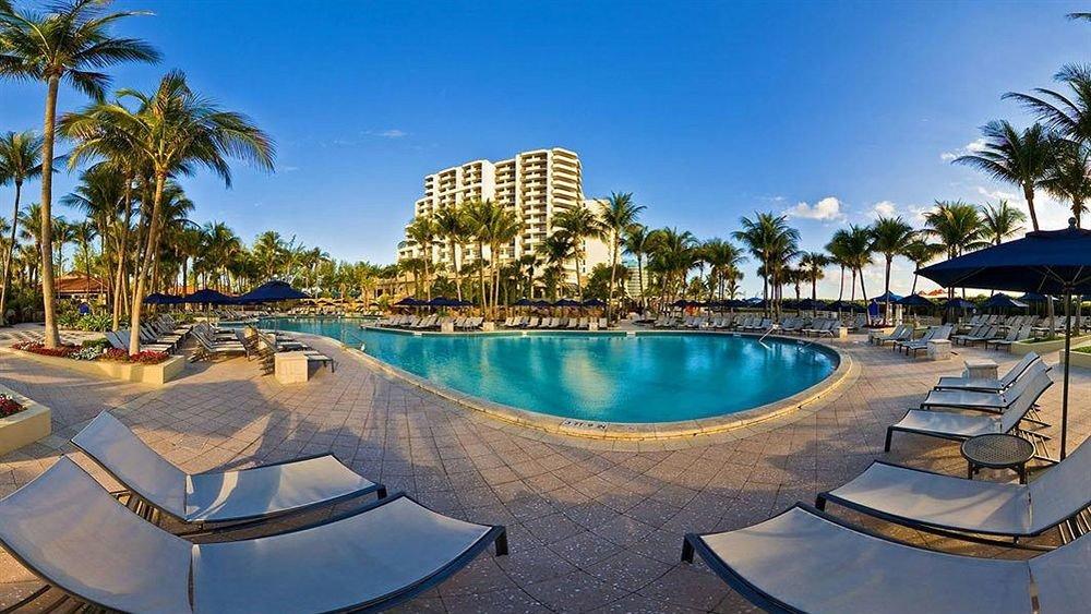Beachfront Exterior Pool Resort sky tree palm water ground swimming pool leisure Beach property condominium resort town lined Villa marina caribbean shore empty sandy swimming day