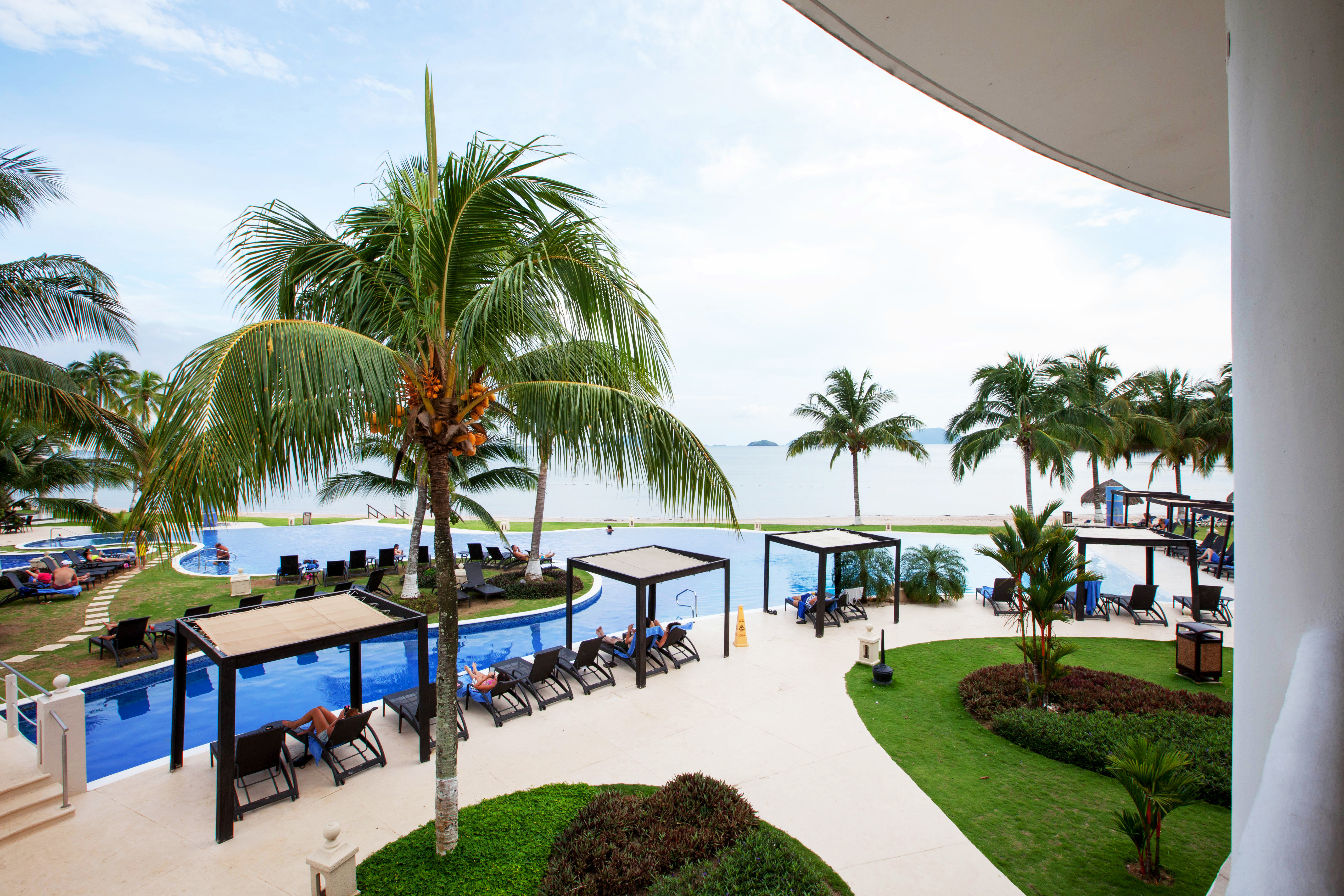Beachfront Family Play Pool Resort sky tree grass palm leisure property caribbean swimming pool arecales Beach condominium Villa home palm family tropics Garden