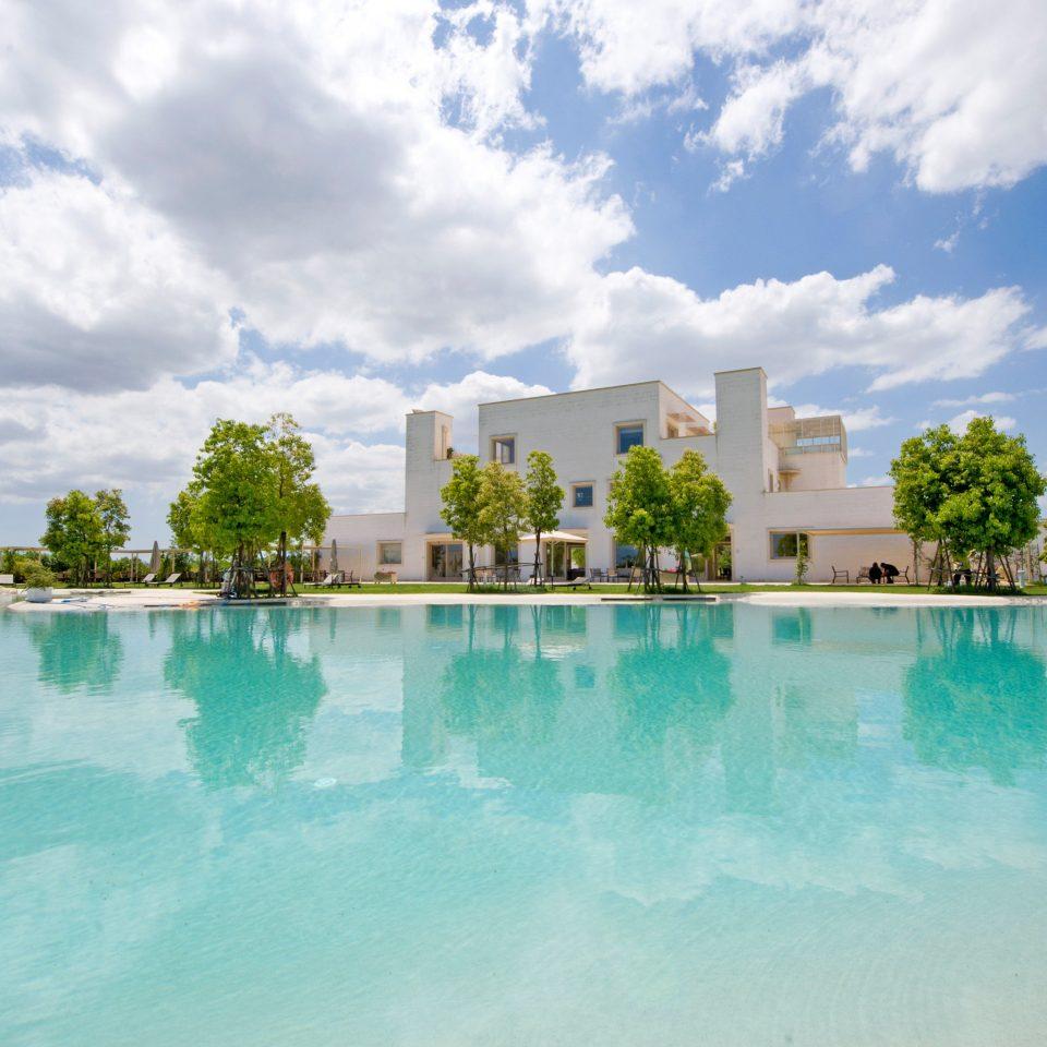 Beach Beachfront Grounds sky water swimming pool Nature Resort Sea condominium Lake Lagoon shore day