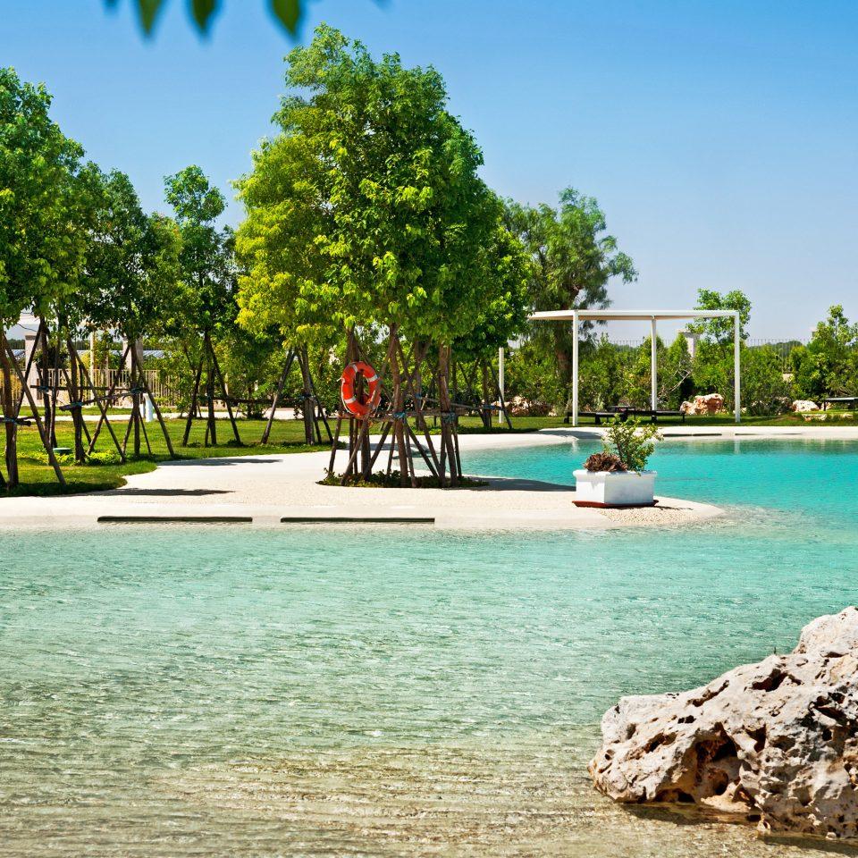 Beach Beachfront Grounds sky tree water leisure Nature rock Sea Resort swimming pool Lagoon park shore reef