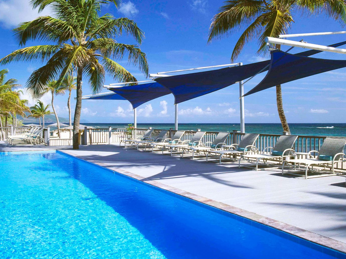 Beachfront Hip Lounge Luxury Tropical tree sky water umbrella Pool palm swimming pool leisure Beach property Resort caribbean lawn condominium marina blue Sea Ocean Lagoon lined resort town arecales swimming Villa Water park atoll shade shore