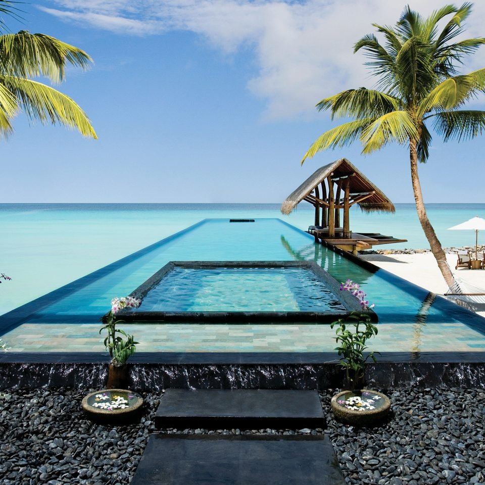 Beach Beachfront Hotels Luxury Pool Romance Romantic Trip Ideas Tropical Wellness tree swimming pool leisure palm caribbean Sea Ocean Resort plant Lagoon arecales Villa tropics shore sandy