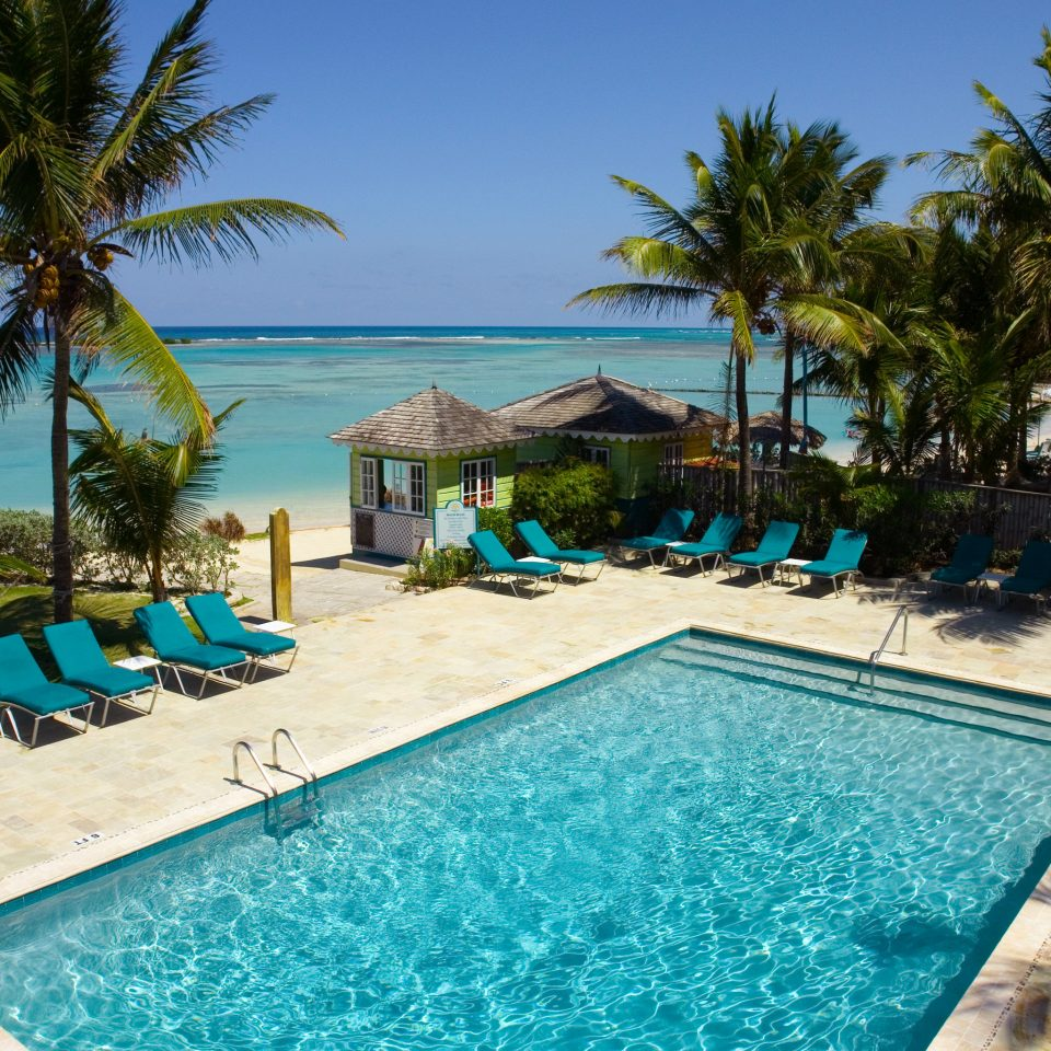 Beach Beachfront Island Pool tree palm sky umbrella Resort water ground swimming pool property leisure caribbean Ocean Villa lined resort town Sea Lagoon arecales swimming condominium shade sandy