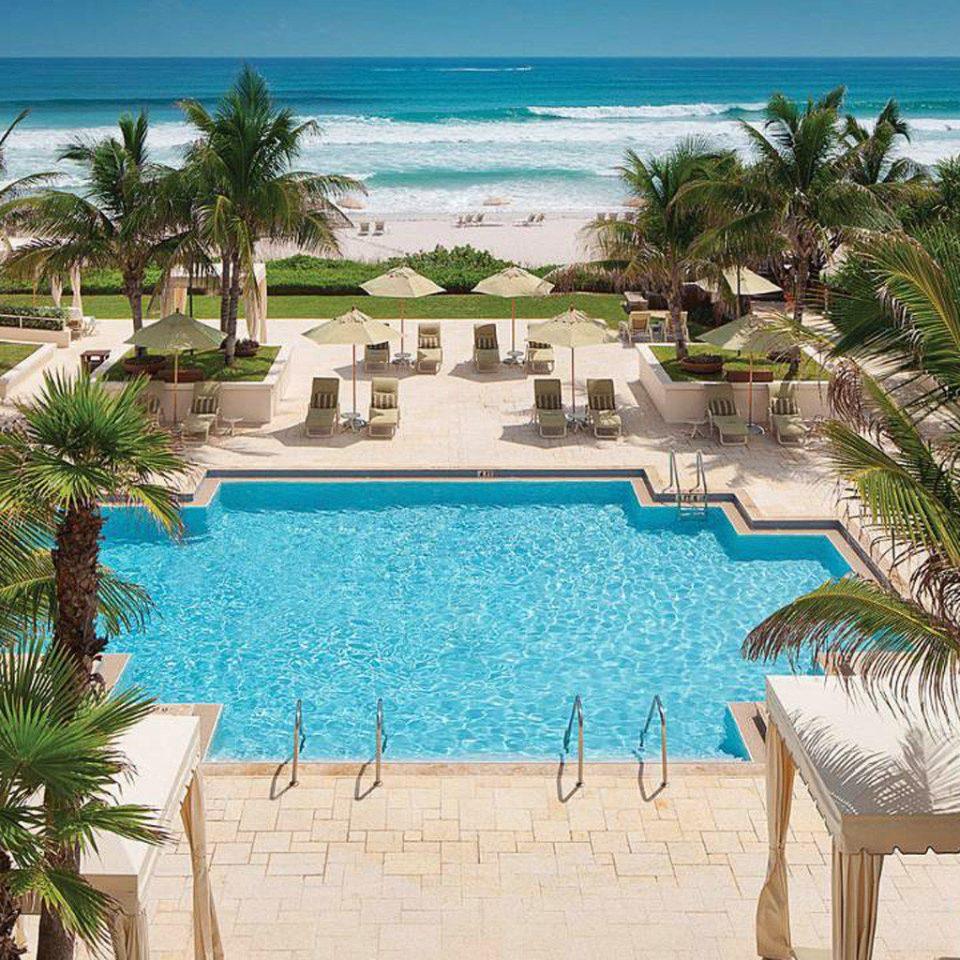 Beachfront Lounge Pool Tropical palm tree Resort swimming pool property plant leisure Beach Ocean caribbean arecales Villa Lagoon mansion hacienda tropics shade sandy shore