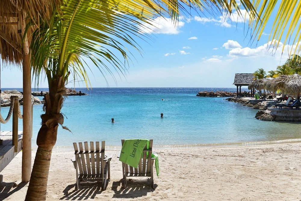 Beach Beachfront Luxury Ocean water sky ground umbrella chair palm leisure caribbean Sea Resort arecales shore plant tropics Lagoon tree sandy lined shade day