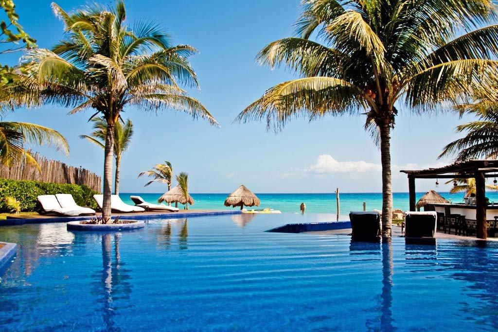 Beachfront Luxury Pool tree water sky palm Beach leisure Resort swimming pool caribbean arecales Ocean Sea Lagoon tropics swimming lined plant shore surrounded sandy