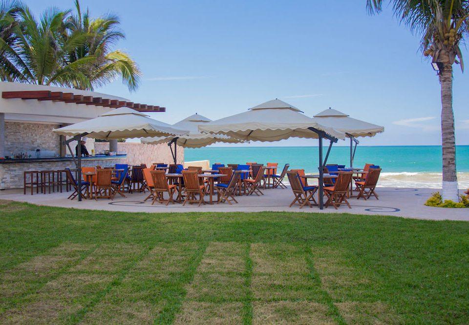 Beachfront Patio Resort sky grass tree Beach leisure property lawn caribbean swimming pool walkway Villa Sea shore palm lined shade