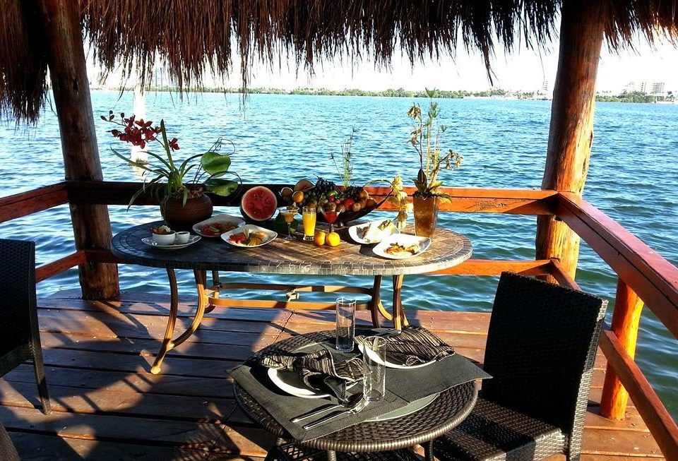 Boutique Dining Drink Eat Waterfront water chair leisure Beach Boat vehicle yacht Ocean Resort watercraft restaurant shore overlooking lined