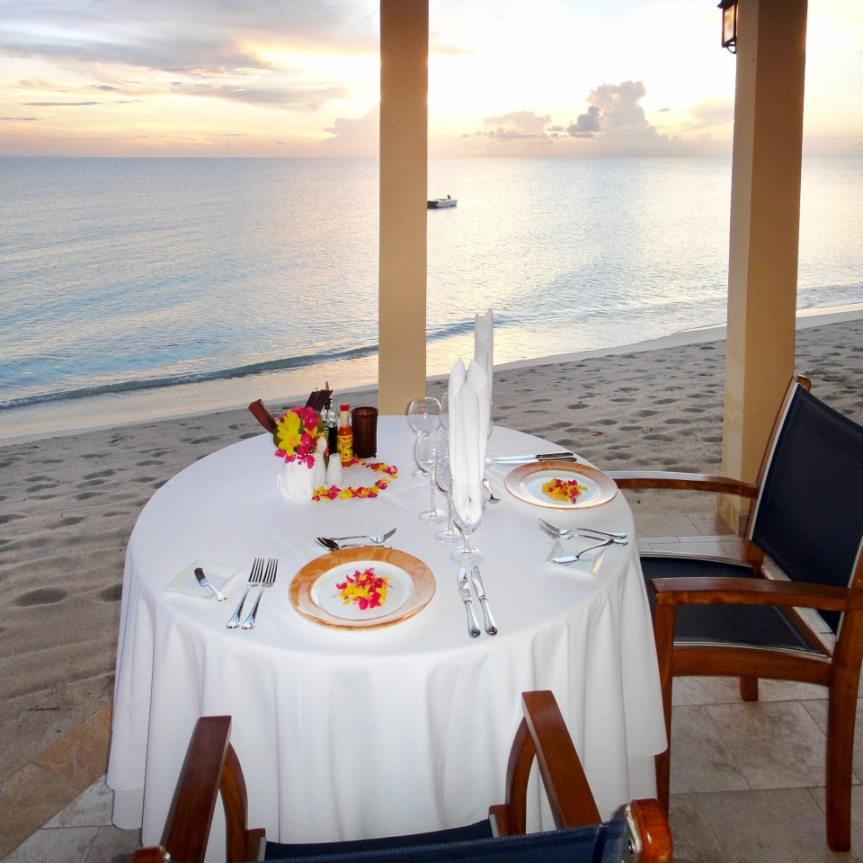 Beach Dining Drink Eat Family Honeymoon Island Romance Romantic Tropical Waterfront water chair Ocean restaurant ceremony Boat vehicle yacht overlooking shore set dining table