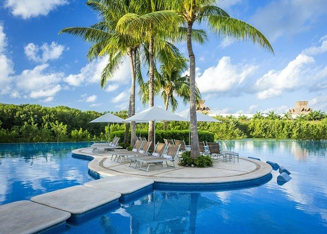 water tree sky Boat Resort swimming pool Pool Lake property leisure caribbean Beach River plant arecales Lagoon resort town palm condominium Villa swimming shore surrounded
