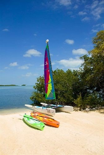 Beach Ocean Outdoor Activities sky ground Boat sailing vehicle sailboat sail watercraft surfboard boating Sea windsurfing transport surfing equipment and supplies wind paddle sports mast kayak sand shore sandy