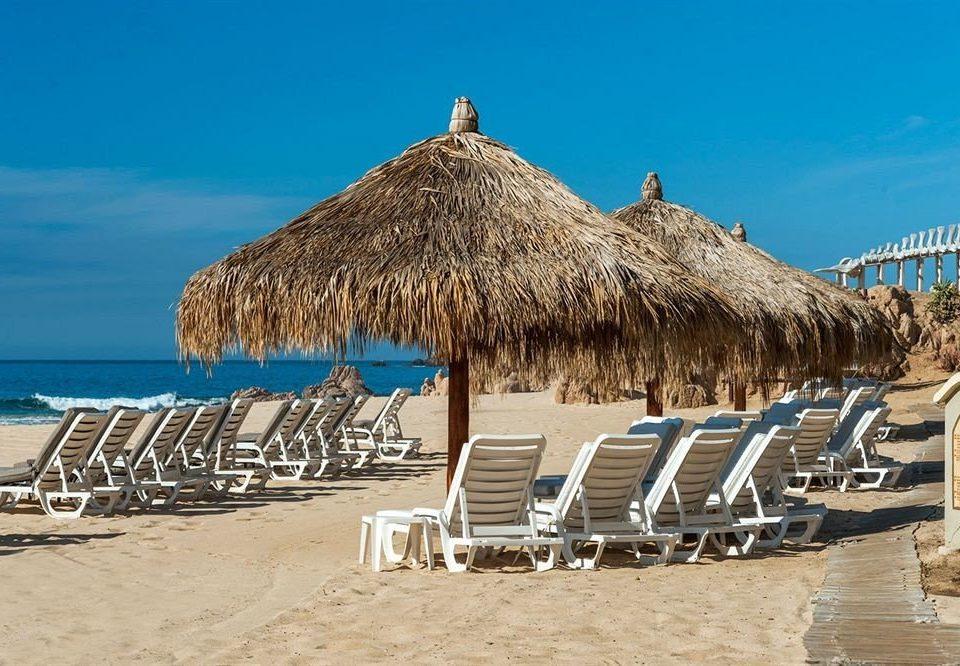 Beach Budget Resort Tropical Waterfront ground sky chair umbrella Sea lawn Coast Ocean sand hut lined cape boardwalk sandy roof line day