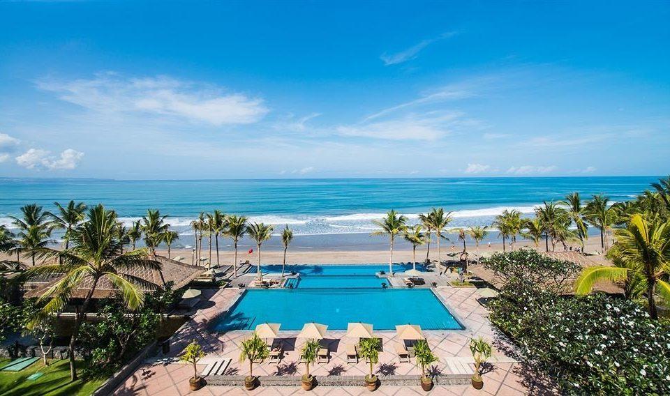 sky Beach umbrella Resort caribbean palm Sea Ocean Nature swimming pool lawn Lagoon shore arecales Coast tropics sandy Deck lined day shade