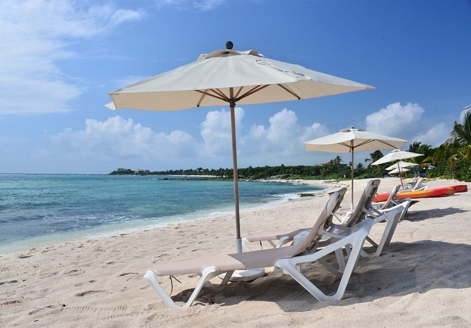 Beach Tropical sky umbrella chair ground lawn leisure Sea Nature shore Ocean Coast wind caribbean vehicle empty set shade day sandy lined Deck