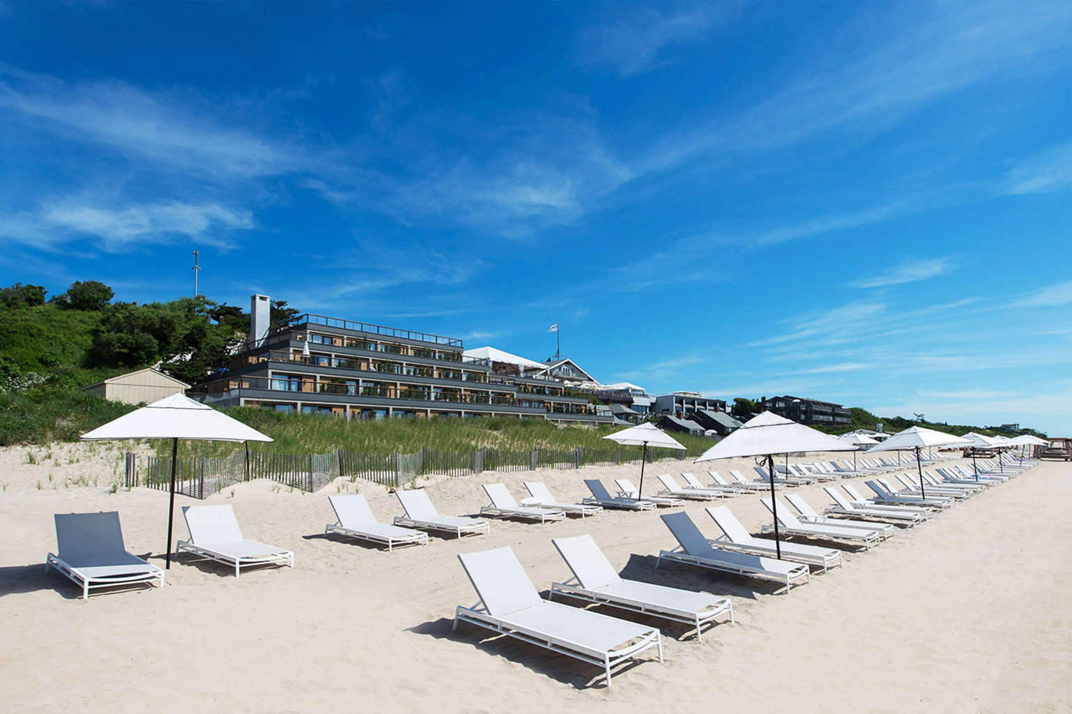 Beach Exterior Hotels Resort sky umbrella chair Sea Coast shore Ocean lawn walkway dock marina boardwalk cape day sandy sunny lined shade