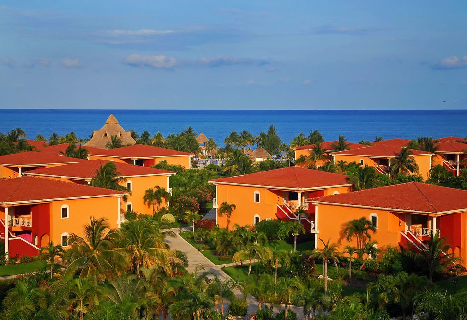 sky building tree house Town Resort Coast Village Beach Sea orange lush Garden bushes hillside