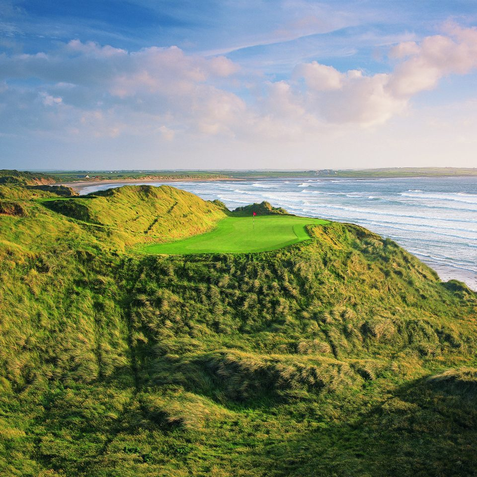 Golf Natural wonders Outdoors Scenic views Sport Waterfront Wellness sky grass habitat Coast Nature green shore Sea cliff Ocean horizon hill rock cloud Beach terrain lush landscape grassy cape hillside day highland