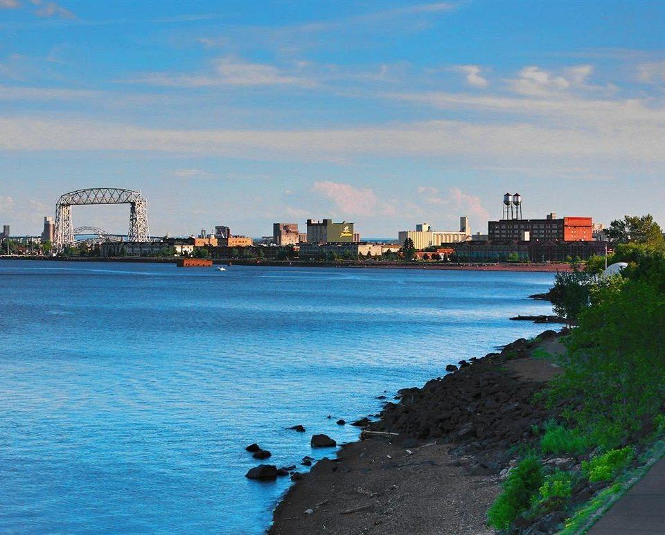 sky water Sea shore Coast horizon landmark scene Beach Ocean River skyline dusk cityscape tower Harbor