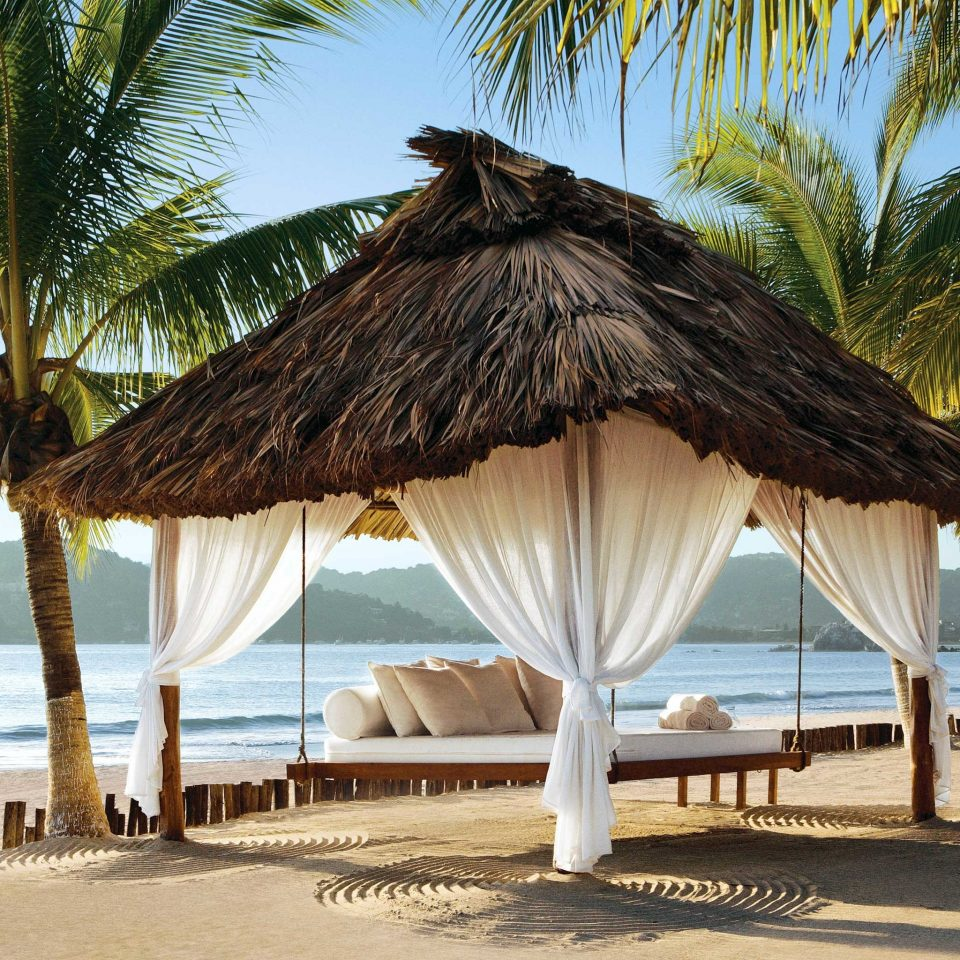 Beach Honeymoon Lounge Modern Romance Romantic Rustic Scenic views Tropical Waterfront water tree umbrella chair palm plant caribbean Sea palm family Ocean tropics arecales Resort sandy Coast lawn shore shade