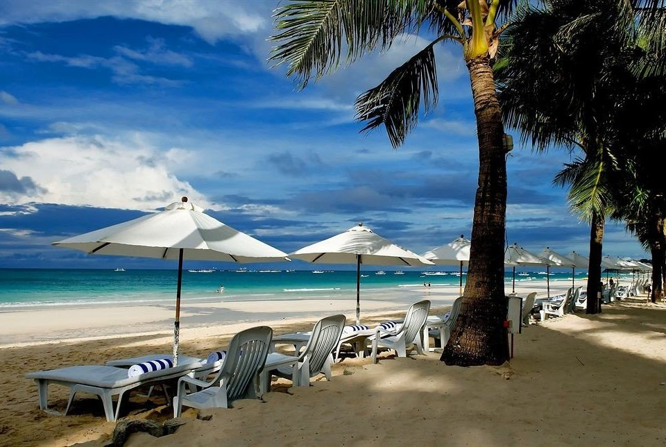 sky water umbrella Beach tree chair ground shore Sea lawn Ocean lined Coast caribbean arecales Nature tropics palm Island cape shade couple Lagoon sandy line swimming