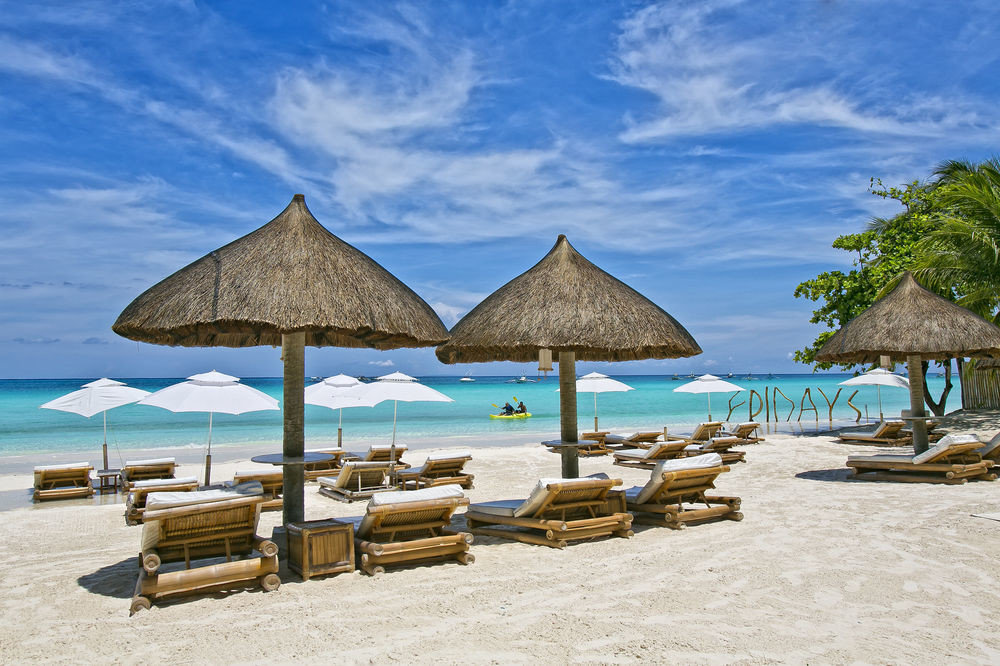 umbrella chair Beach sky water ground lawn Sea Ocean shade Resort caribbean Coast Island Lagoon lined sandy empty set day shore