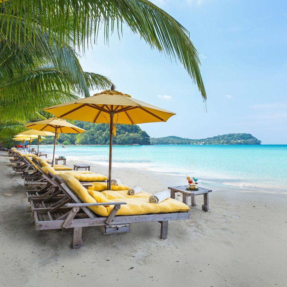 Beach sky umbrella water chair Sea caribbean Ocean shore arecales tropics lawn Resort Coast Island Lagoon sand palm sandy lined day