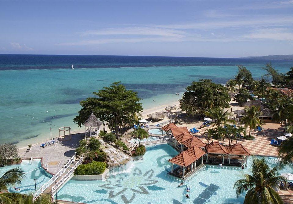 water sky umbrella Ocean Beach chair Nature property Resort caribbean Sea Coast lawn Lagoon cape reef cove swimming pool overlooking tropics shore Island beautiful lined day swimming
