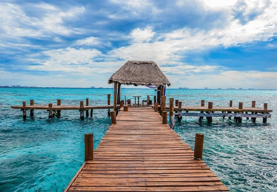 Modern Ocean Overwater Bungalow Scenic views Tropical Waterfront water sky pier scene umbrella chair Beach wooden Sea shore caribbean Resort Lagoon Island swimming pool Coast dock walkway boardwalk swimming lined sandy day