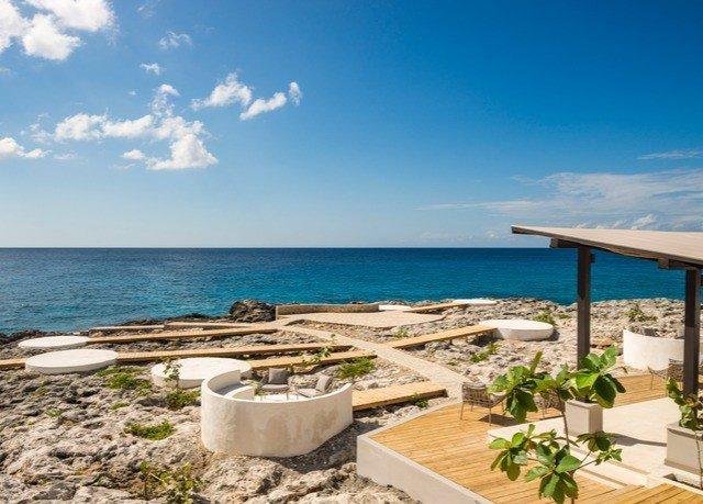 sky water ground umbrella Beach chair property Nature leisure Ocean Sea shore Resort Coast lawn caribbean Villa cape sunny set sandy day Island