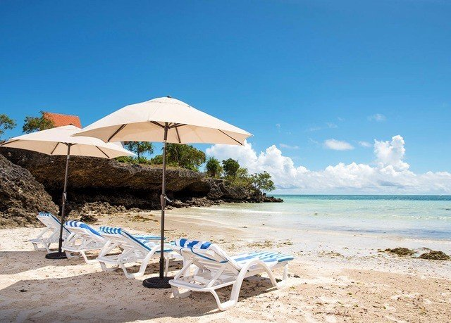 sky umbrella ground Beach Nature chair shore leisure Resort Sea Ocean caribbean lawn Lagoon Coast sandy day shade