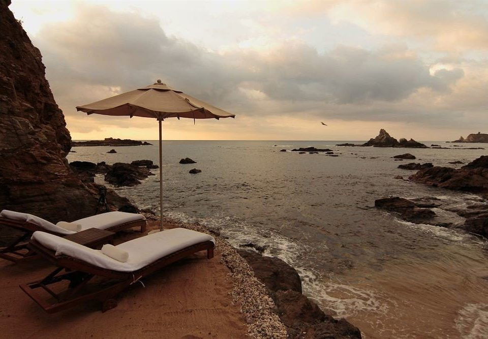 Beach Lounge Resort Waterfront sky mountain water shore Coast Sea Ocean Nature horizon sand rock cape landscape wave Sunset cove dusk sandy
