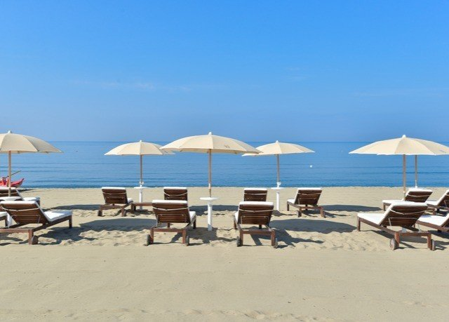 umbrella sky chair Beach ground lawn Nature shore Resort Sea Coast Ocean walkway sand sandy day seat lined shade