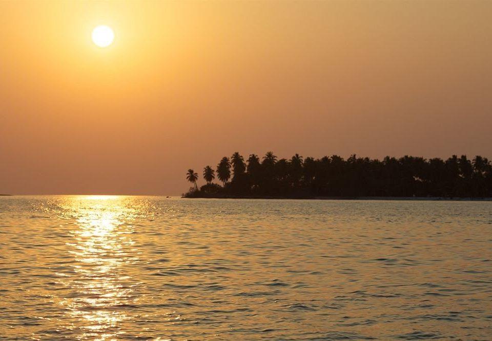 water sky Sunset horizon atmospheric phenomenon Sun Sea sunrise shore dawn morning afterglow Ocean Nature evening dusk sunlight Beach Coast sailing vessel distance