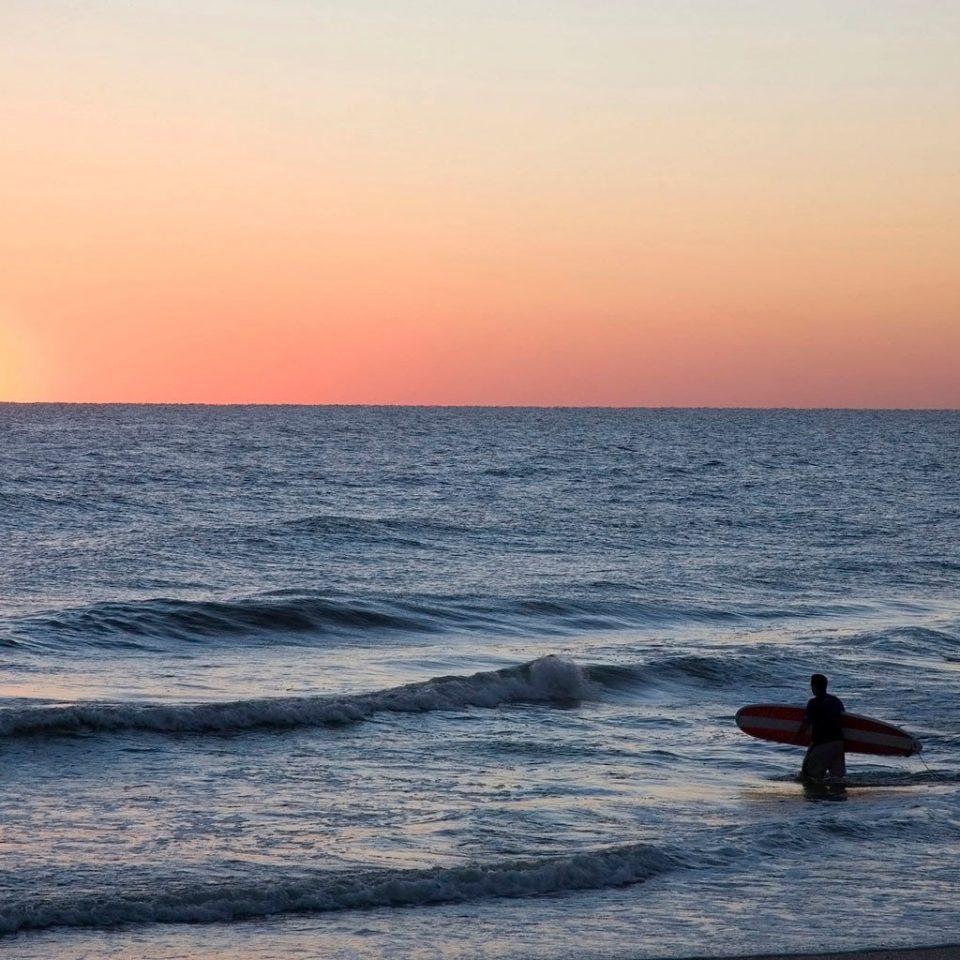 Beach Ocean Outdoor Activities Romance Sport Sunset water sky Sea shore horizon sunrise wind wave wave Coast morning dawn Nature dusk evening carrying