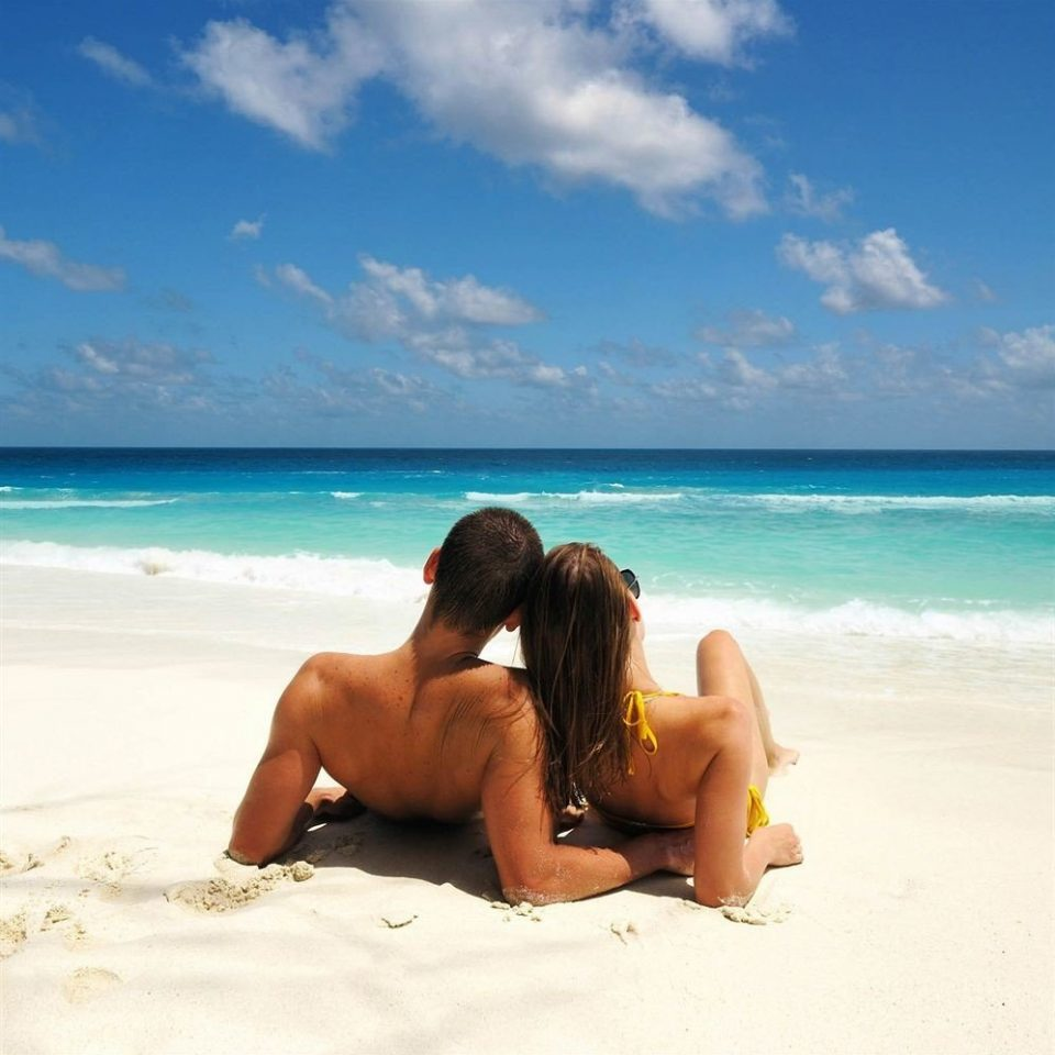 sky water Beach sitting sun tanning Sea shore Ocean caribbean Nature sand leg Coast interaction