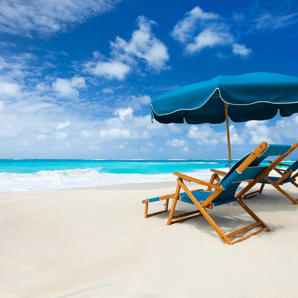 sky umbrella Beach chair water blue leisure Sea shore Ocean Nature caribbean Coast sand sandy day