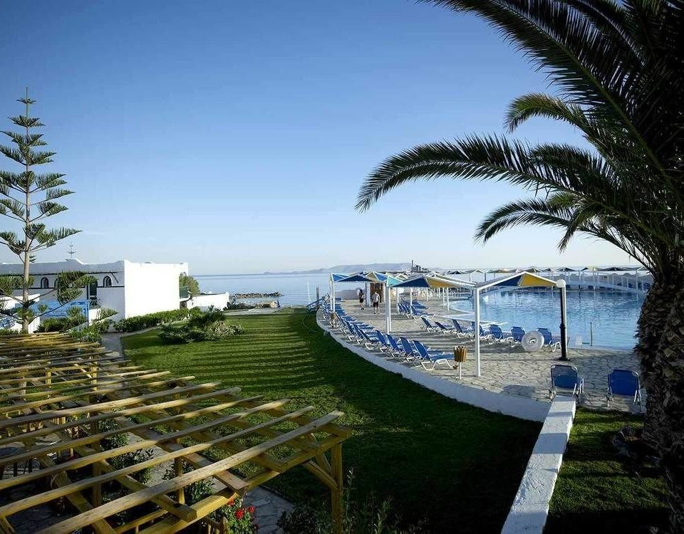 sky tree grass marina Coast walkway dock Resort Sea arecales Ocean Beach condominium plant palm lined shore