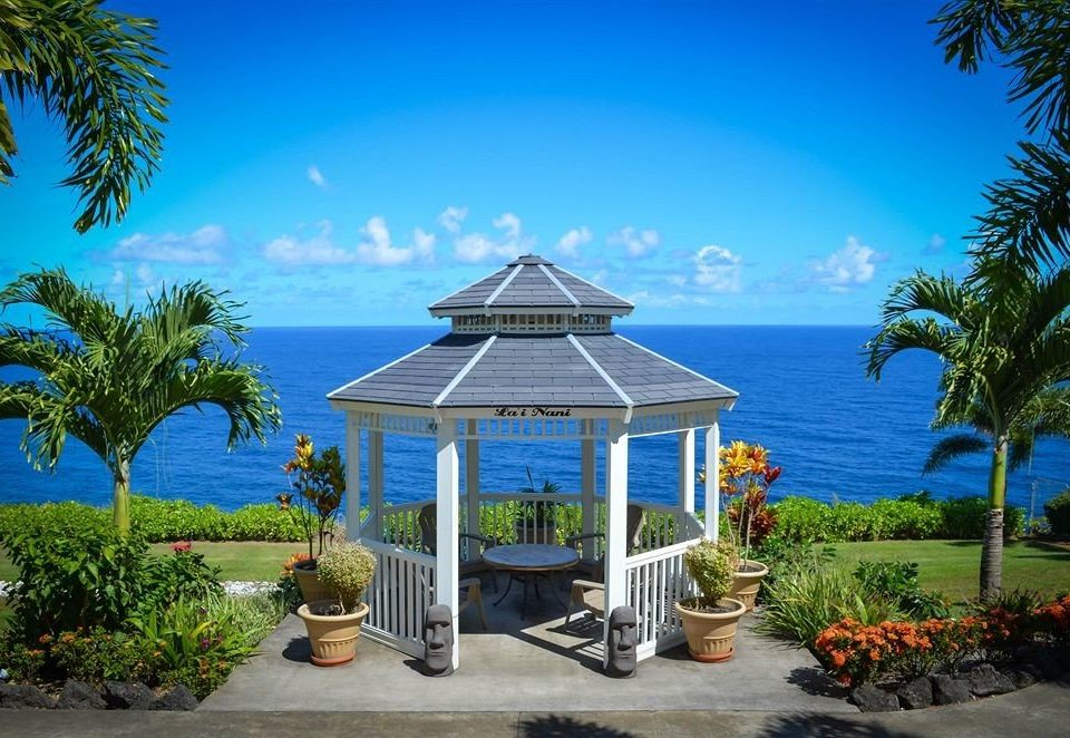 Deck Grounds Patio Resort Scenic views tree palm sky building Beach property caribbean Ocean plant arecales swimming pool Villa Pool Garden beautiful shade lined overlooking