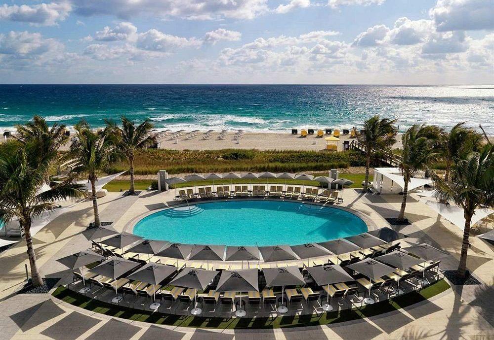 sky water Beach umbrella chair swimming pool Ocean leisure property lawn Resort caribbean Pool Nature Villa condominium shore mansion Sea lined Deck palm line swimming day sandy Island