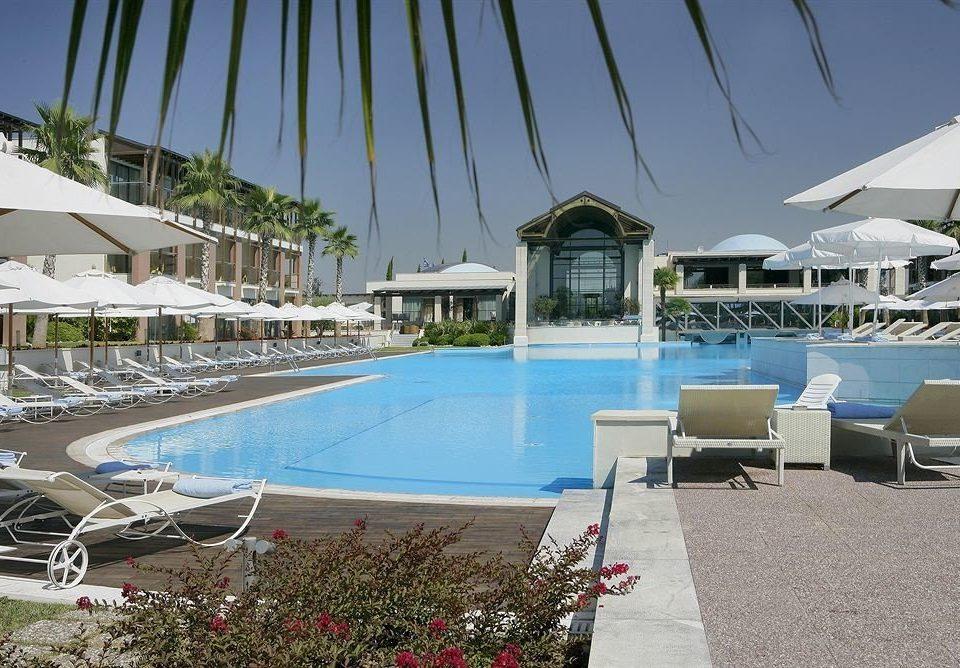 umbrella lawn chair swimming pool Beach property leisure Resort marina condominium Villa dock Deck set sandy lined shore shade