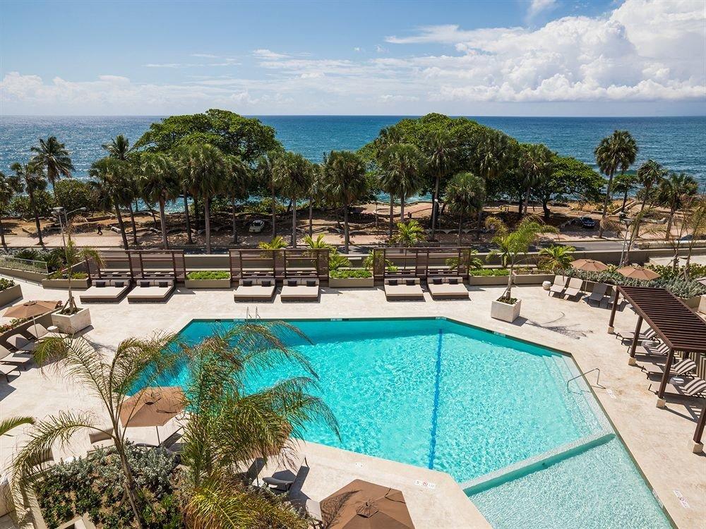 sky tree ground Beach umbrella swimming pool chair property Resort leisure Pool Villa lawn backyard Lagoon condominium mansion sandy Garden swimming
