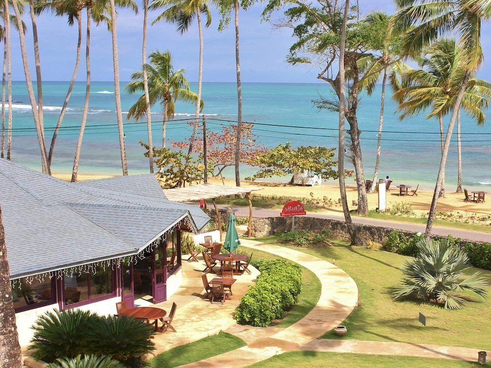 tree sky water umbrella grass palm Resort property Beach caribbean arecales plant Villa lawn marina Pool swimming pool condominium Garden shade shore