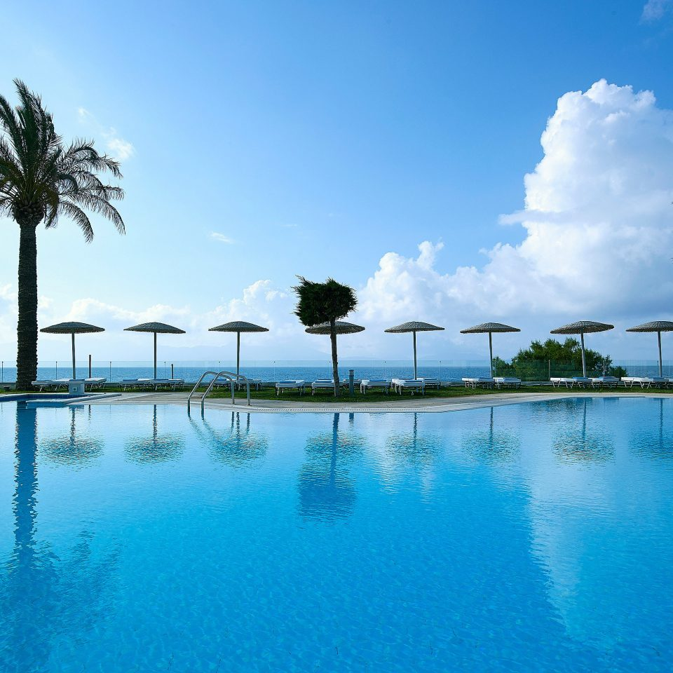 tree water sky swimming pool Nature Pool Resort Ocean arecales Sea Lagoon palm Beach Lake pond caribbean surrounded swimming