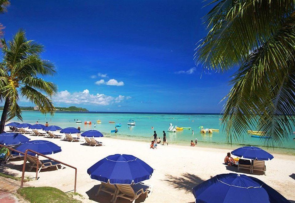 umbrella Beach tree sky water chair palm shore leisure lawn Nature caribbean Resort swimming pool Ocean Sea accessory arecales Lagoon lined blue tropics shade enjoying day swimming sandy