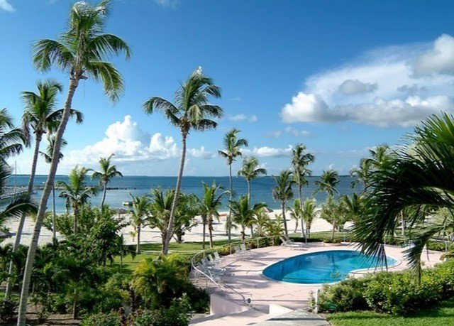 tree palm sky Resort Beach Ocean property Pool caribbean swimming pool arecales Villa condominium plant lawn Lagoon tropics palm family sandy shade lined shore