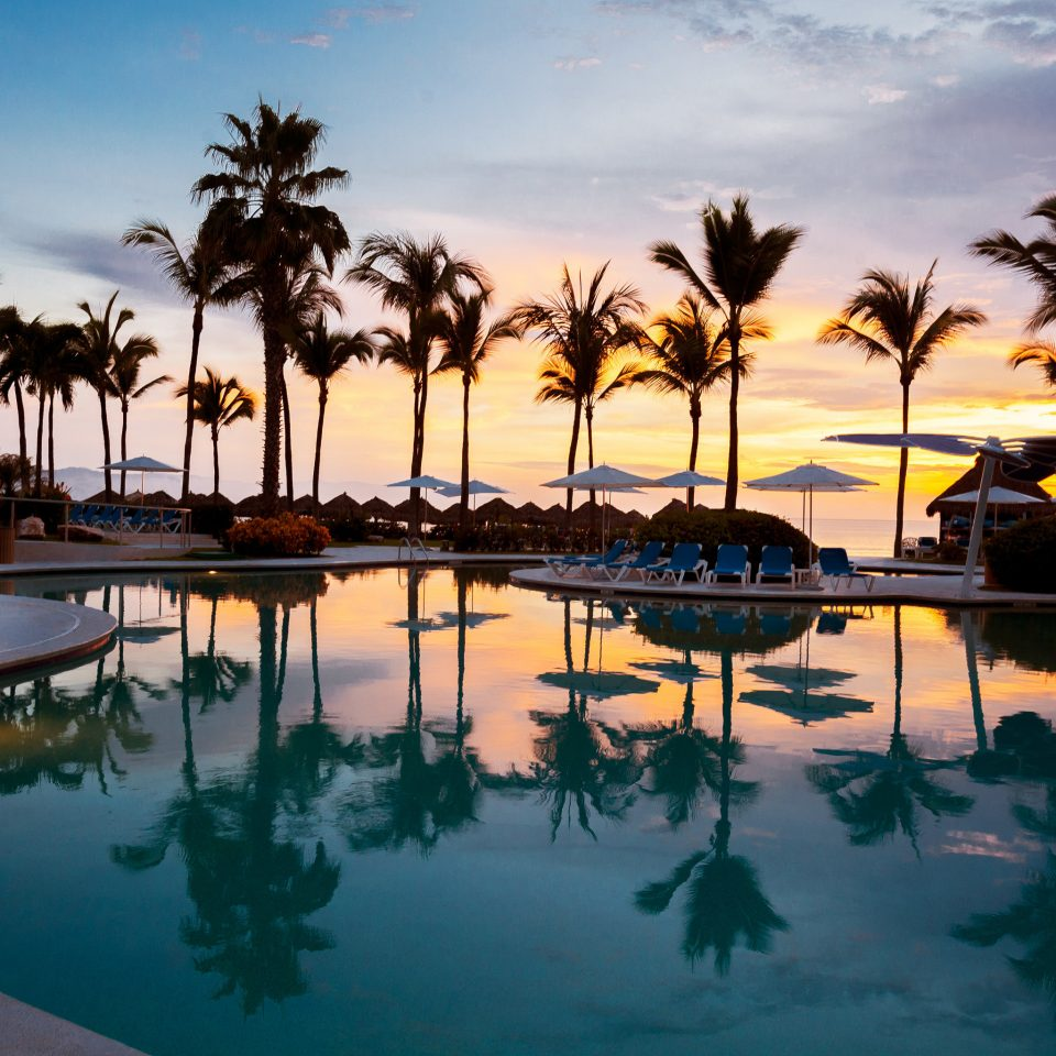 Pool Tropical Waterfront sky water palm tree Resort Ocean Beach Sea arecales Sunset Lagoon dusk plant evening caribbean tropics palm family lined shore sandy