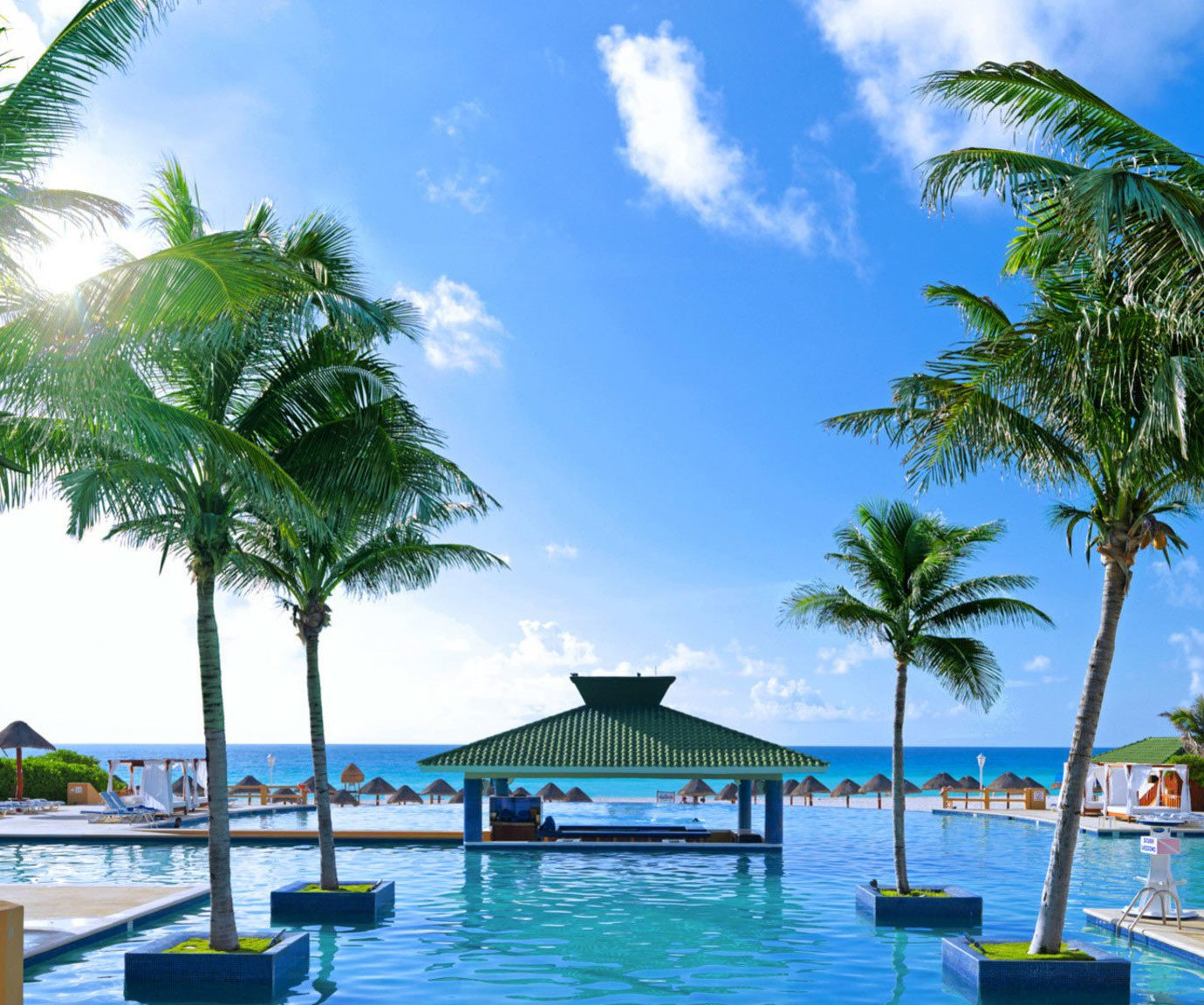 tree sky palm water umbrella chair Resort Beach leisure caribbean swimming pool Pool lined arecales plant tropics resort town Lagoon lawn palm family Sea Villa shade sunny swimming