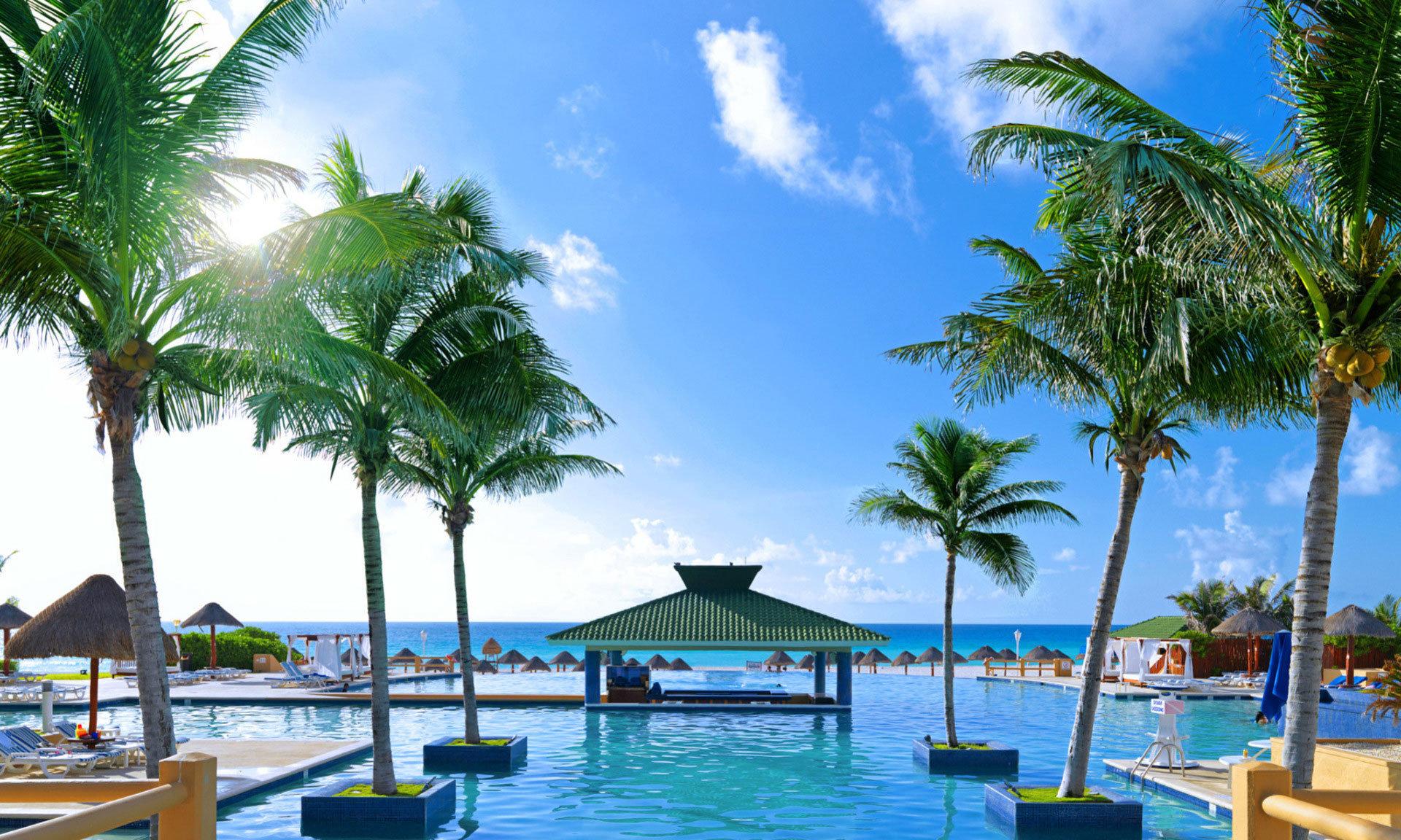 tree sky palm water umbrella chair Resort Beach leisure caribbean swimming pool Pool lined arecales plant tropics resort town Lagoon lawn palm family Sea Villa shade sunny swimming