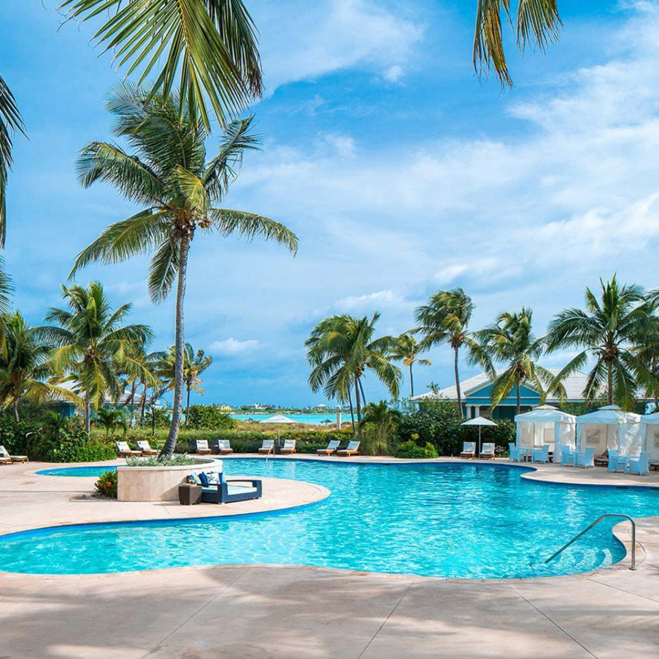 tree palm sky Pool Beach water Resort ground swimming pool swimming property leisure caribbean arecales lined Lagoon Villa Sea tropics condominium blue plant sunny sandy surrounded